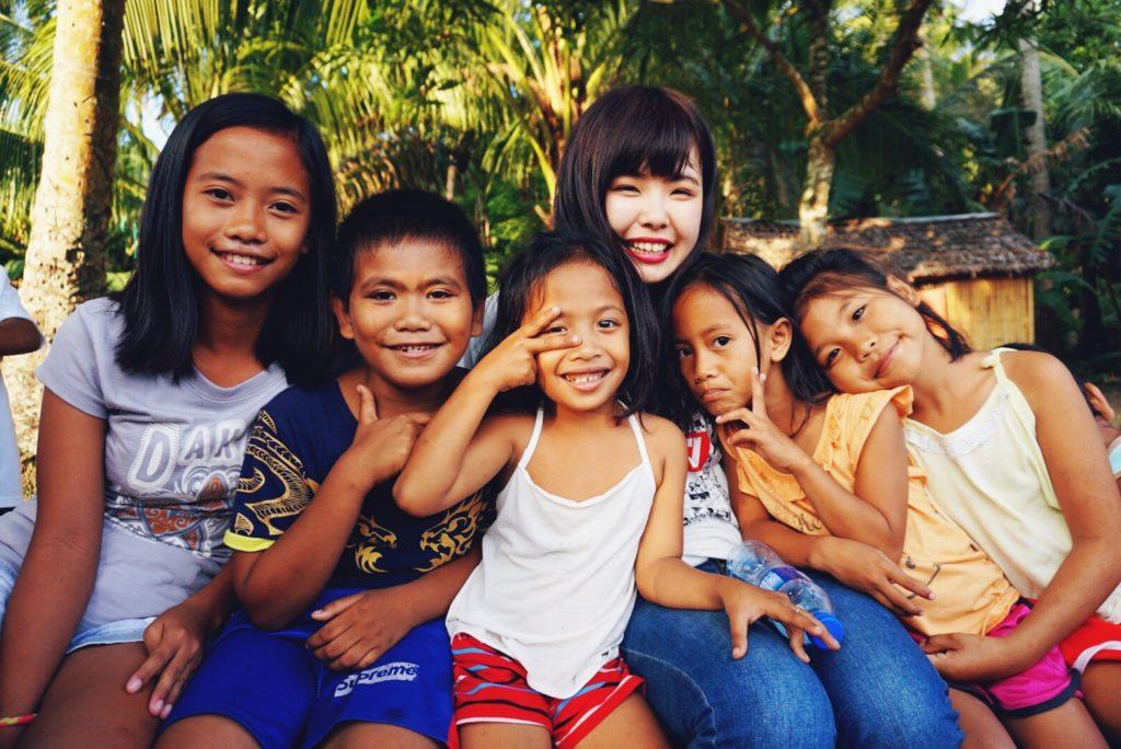 子どもたち笑顔いっぱいで写る大学生。スタディツアーでは、現地の子どもたちと交流する時間がたっぷり!
